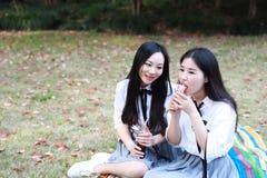 2 молодых азиатских китайских милых девушки костюм студента носки в лучших другах школы усмехается вода колы питья смеха едят мор Стоковая Фотография