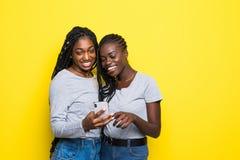 2 молодых африканских женщины выражая ободрение или сюрприз пока оба используя сотовый телефон изолированный на желтой предпосылк стоковая фотография
