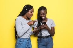 2 молодых африканских женщины выражая ободрение или сюрприз пока оба используя сотовый телефон изолированный на желтой предпосылк стоковое фото