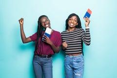 2 молодых африканских женщины с билетами на самолет готовыми для перемещения изолированной на пастельной голубой предпосылке стоковое изображение rf
