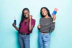 2 молодых африканских женщины с билетами на самолет готовыми для перемещения изолированной на пастельной голубой предпосылке стоковые фотографии rf
