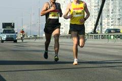 Гонка марафона идущая, ноги людей на дороге города 2 молодых бегуна немного метров от прибытия трудного марафона до конца стоковое фото