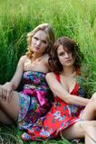 2 молодых белокурых девушки и коричнев-с волосами женщина в ярких платьях представляя в лете паркуют в высокорослой траве Стоковое Изображение RF