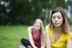 2 молодых белокурых женщины выполняют тренировку для гибкости в парке Стоковые Изображения