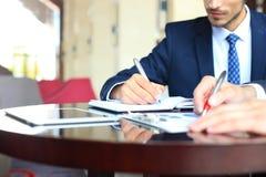 2 молодых бизнесмена анализируя финансовый документ на встрече Стоковое фото RF