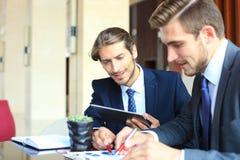 2 молодых бизнесмена анализируя финансовый документ на встрече Стоковое Фото
