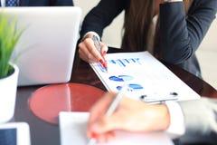 2 молодых бизнесмена анализируя финансовый документ на встрече Стоковые Фотографии RF