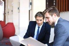 2 молодых бизнесмена анализируя финансовый документ на встрече Стоковые Изображения RF