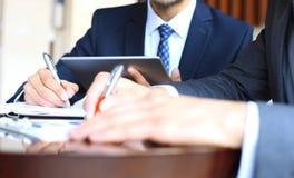 2 молодых бизнесмена анализируя финансовый документ на встрече Стоковая Фотография RF