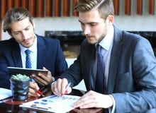 2 молодых бизнесмена анализируя финансовый документ на встрече Стоковое Изображение RF