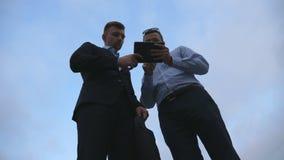 2 молодых бизнесмена говоря и используя ПК таблетки внешний Бизнесмены работая на цифровой таблетке снаружи с небом на Стоковое Фото