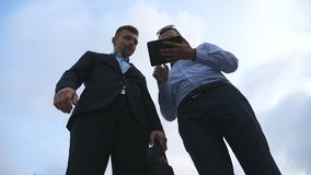 2 молодых бизнесмена говоря и используя ПК таблетки внешний Бизнесмены работая на цифровой таблетке снаружи с небом на Стоковые Изображения