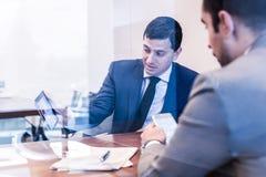 2 молодых бизнесмена используя электронные устройства на деловой встрече Стоковое Изображение RF