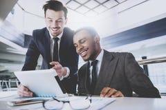 2 молодых бизнесмена обсуждают план работы, пока смотрящ документы Стоковые Фотографии RF