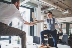 2 молодых бизнесмена со шпагами в офисе, имеющ потеху Концепция конкуренции стоковое фото rf
