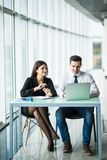 2 молодых бизнесмены сидя на таблице с портативным компьютером внутри офиса Стоковые Изображения RF