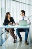 2 молодых бизнесмены сидя на таблице с портативным компьютером внутри офиса Стоковое Изображение