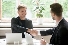 2 молодых бизнесмены трясут руки в офисе Стоковые Изображения