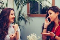 2 молодых бизнес-леди аранжируют встречу через мобильный телефон с их бизнес-партнерами стоковое фото