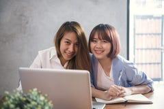 2 молодых бизнес-леди сидя на таблице в кафе Азиатские женщины используя компьтер-книжку и чашку кофе Фрилансер работая в кофейне Стоковое Изображение RF