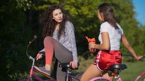 2 молодых велосипедиста связывают и смеются над на задействуя отключении в парке, на солнечный летний день Стоковые Изображения