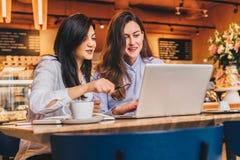 2 молодых веселых коммерсантки в рубашках сидя в кафе на таблице и используя компьтер-книжку Девушка указывает на экран компьютер Стоковые Фотографии RF