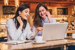 2 молодых веселых коммерсантки в рубашках сидя в кафе на таблице и используя компьтер-книжку Девушка указывает на экран компьютер Стоковое Изображение RF
