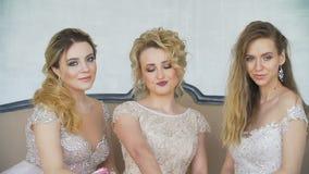 3 молодых взрослых девушки представляя на камере сидя на софе дома акции видеоматериалы