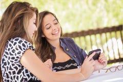 2 молодых взрослых подруги используя их умный сотовый телефон Стоковое фото RF