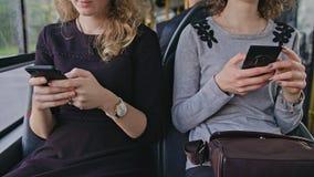 2 молодых дамы используя Smartphones на шине Стоковое фото RF