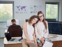 2 молодых девушки дела в белых блузках на офисе утомлены Стоковое Изображение RF