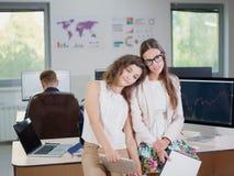 2 молодых девушки дела в белых блузках на офисе утомлены Стоковые Фото