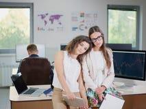 2 молодых девушки дела в белых блузках на офисе утомлены стоковое изображение