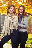 2 молодых девушки моды в белых рубашке и шарфе идя в город Стоковые Изображения RF