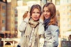 2 молодых девушки моды в белых рубашке и шарфе идя в улицу города Стоковая Фотография
