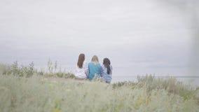 3 молодых девушки нося длинное платье моды лета беседуют на поле на фоне озера или сток-видео