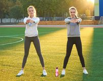 2 молодых девушки спорт делая гимнастику в утре на зеленой траве под открытым небом, рассвет, фитнес, здоровье, спорт Стоковые Фотографии RF