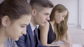 3 молодых дизайнера работают совместно в ярком кафе видеоматериал