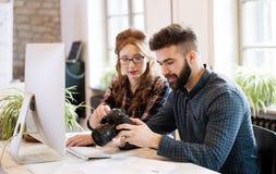 2 молодых дизайнера работая в современном офисе Стоковые Изображения RF