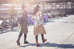 2 молодых друз в стильных пальто и рюкзаках идут на городскую площадь в Казани Стоковое Фото