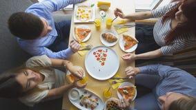 4 молодых друз сидя на кафе и едят завтрак - пиццу, сок, десерты Стоковое Изображение RF