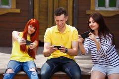 3 молодых друз сидя на стенде пристрастившийся к передвижному видео ga Стоковая Фотография RF