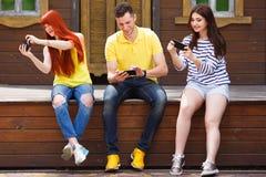 3 молодых друз сидя на стенде пристрастившийся к передвижному видео ga Стоковые Фотографии RF