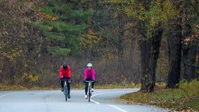 2 молодых женских велосипедиста ехать велосипеды дороги в парке в холодном утре осени Здоровый уклад жизни Стоковое Фото