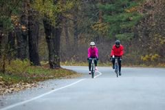 2 молодых женских велосипедиста ехать велосипеды дороги в парке в холодном утре осени Здоровый уклад жизни Стоковое фото RF