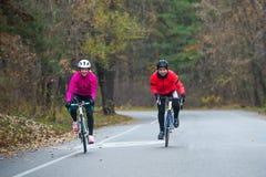 2 молодых женских велосипедиста ехать велосипеды дороги в парке в холодном утре осени Здоровый уклад жизни Стоковая Фотография