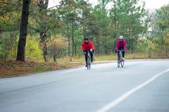 2 молодых женских велосипедиста ехать велосипеды дороги в парке в холодном утре осени Здоровый уклад жизни Стоковые Изображения