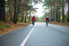 2 молодых женских велосипедиста ехать велосипеды дороги в парке в холодном утре осени Здоровый уклад жизни Стоковые Фото