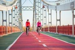 2 молодых женских велосипедиста ехать велосипеды дороги на линии велосипеда моста в холодном солнечном дне осени уклад жизни прин Стоковое Изображение RF