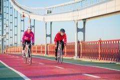 2 молодых женских велосипедиста ехать велосипеды дороги на линии велосипеда моста в холодном солнечном дне осени уклад жизни прин Стоковые Фото